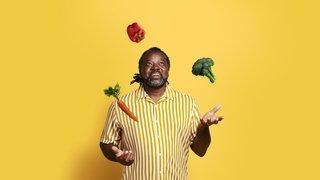 Man juggling fruit and vegetables