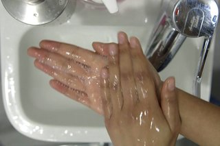 image of rubbing hands together over the sink