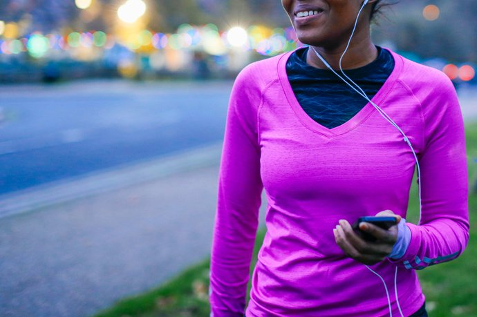 A woman wearing exercise clothing with headphones in