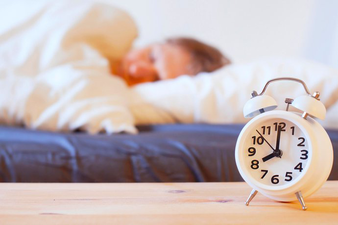White alarm clock with black hands and numbers to right foreground, blurred woman sleeping behind on blow-up bed