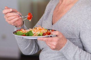 An older person eating a plate of healthy-looking food