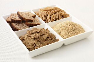 Four bowls containing pasta, bread, rice and bran flakes