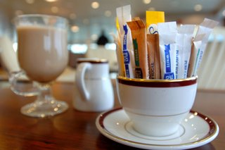A mug full of sachets of sugar and sweeteners