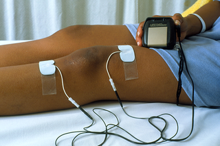 White pads stuck above and below a person's knee. The pads are attached to wires connected to a small handheld TENS machine.