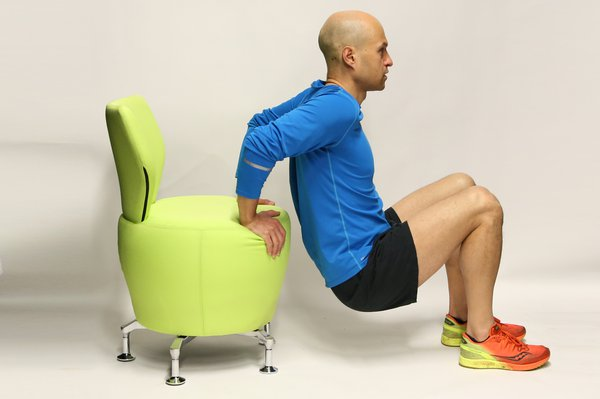 Man with a chair behind him using it to lower himself. His hands are on the chair, his elbows are bent. His knees are bent, his feet are on the floor.