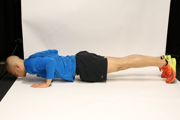 Man lying face down propped up on hands and toes, with legs straight and elbows bent. His body forms a straight line and he is very close to the floor.