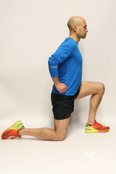 Man kneeling down on his right knee, leaning forwards. He is looking straight ahead and his hands are on his hips.