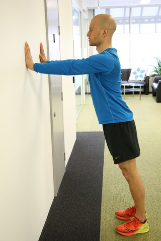 Man standing, touching a wall with his hands. His arms are straight.