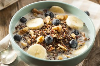 A bowl of muesli with banana slices and blueberries