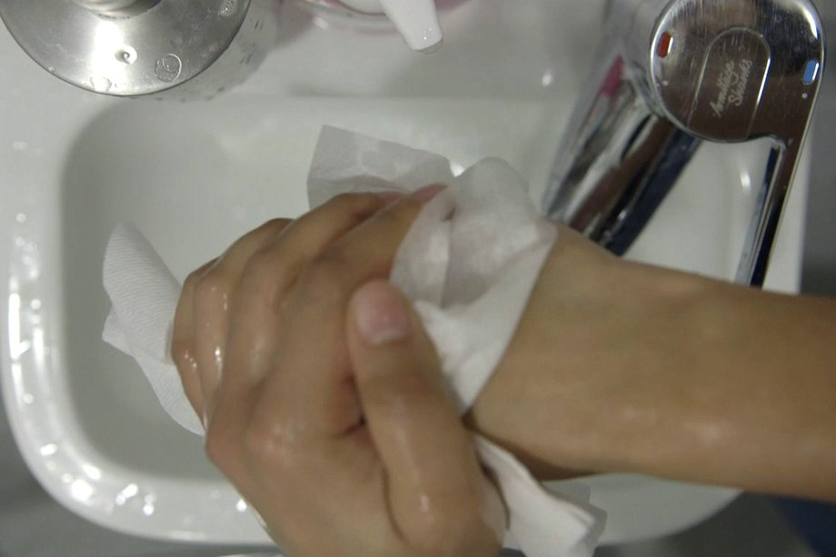image of drying hands with a disposable towel