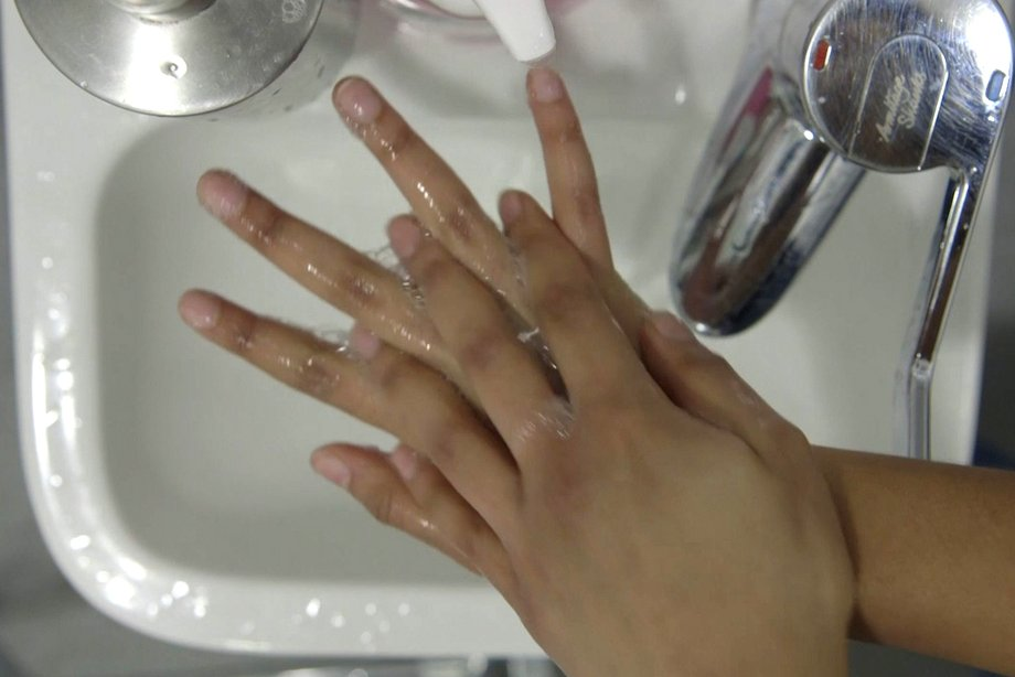 image of cleaning between the fingers over the sink