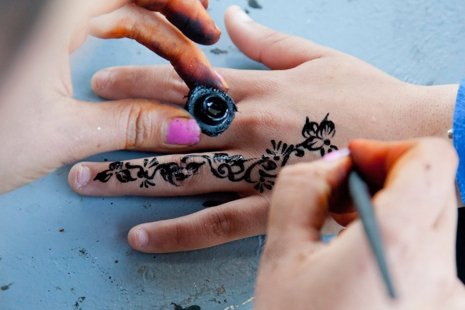 A floral black henna tattoo being painted onto a hand