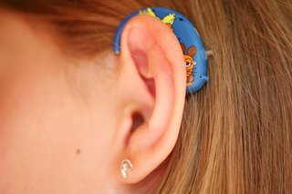 A close-up image of a young person's left ear with a blue hearing aid behind their ear.