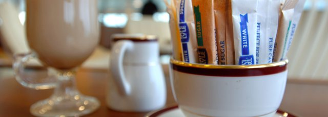 A mug full of sachets of sugar and sweeteners.
