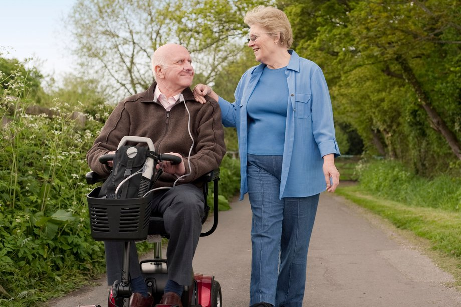 A woman and a man using a mobility scooter on a country lane