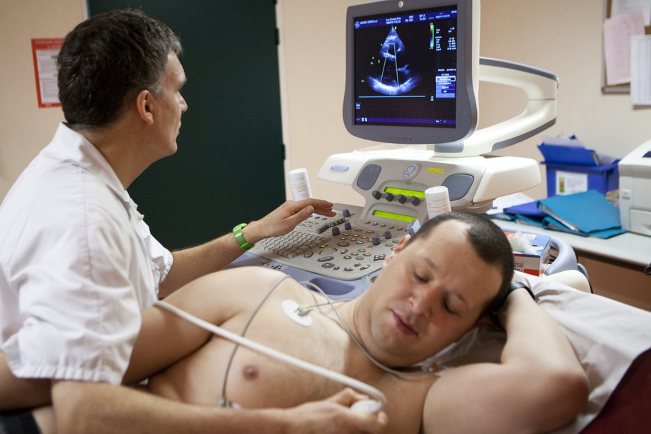 A man having an echocardiogram, with sensors attached to his chest and an image on a monitor