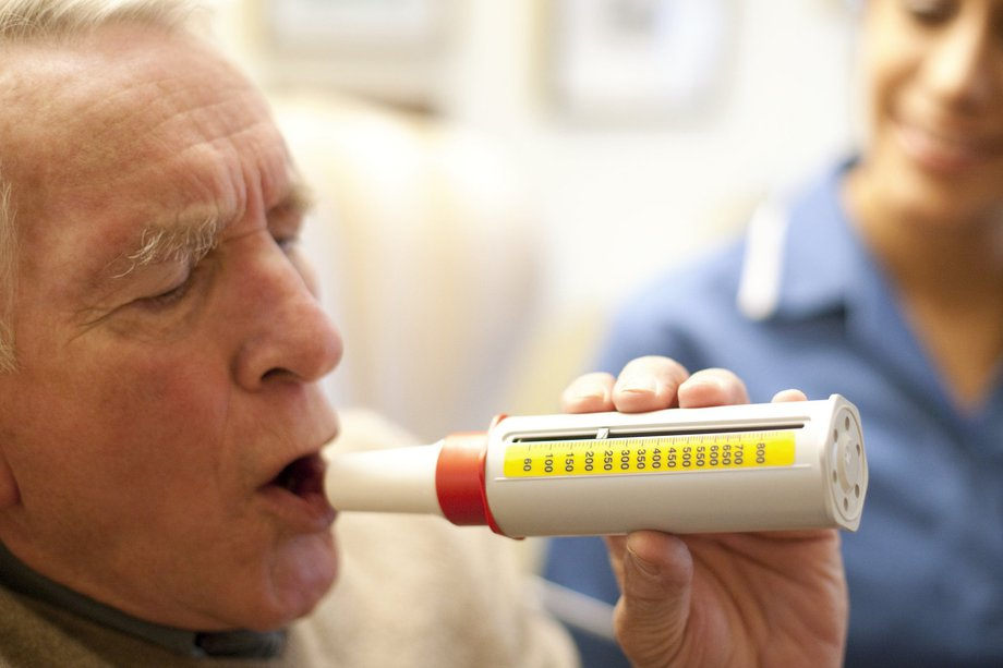Picture of a man using a peak flow meter