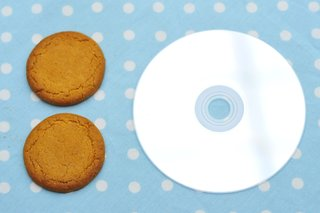 2 ginger nut biscuits next to a CD