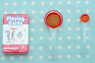 A spoonful of olive oil next to a pack of cards