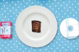 A 100-calorie serving of steak on a plate next to a pack of cards and a CD