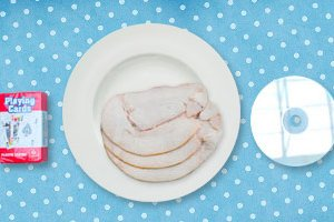 3 turkey slices on a plate next to a pack of cards and a CD