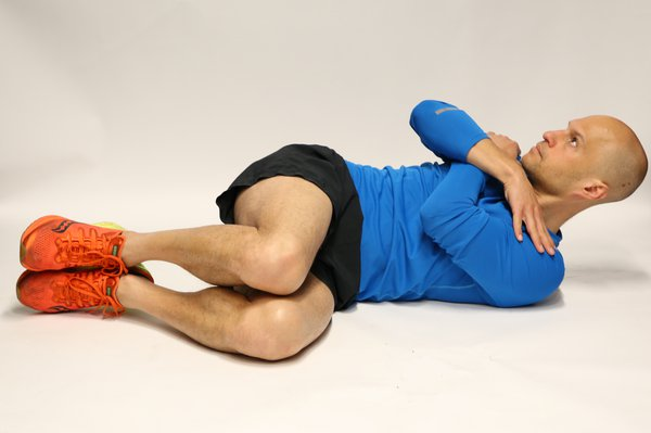 Man lying on back, knees bent and rolled to one side to the floor. Hands are crossed over the chest.