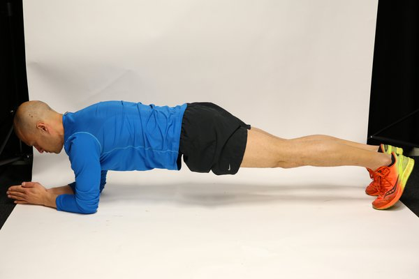 Man lying face down, propped up on forearms and toes, with legs straight and hips raised to create a straight line from head to toe.