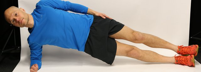Man lying on side propped up on an elbow, with legs and hips raised in straight line from head to toe.