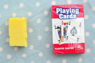 A matchbox-sized piece of cheddar cheese next to a pack of cards