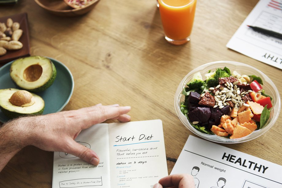 A table with a bowl of salad and a person writing a diet plan