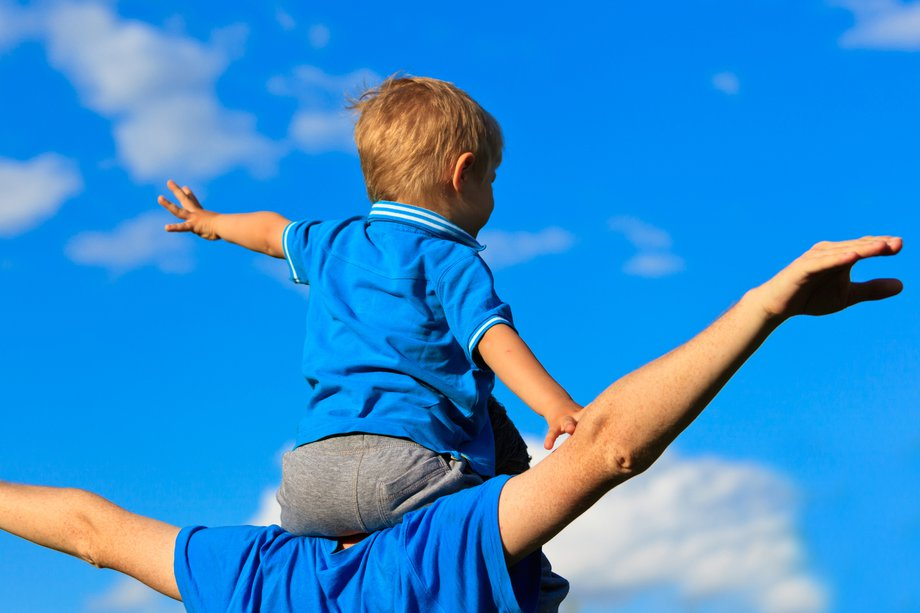 A young child sitting on the shoulders of an adult – both's arms are outstretched