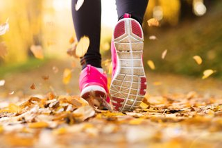 Close-up of a runner's pink running shoes, in autumn leaves on the ground