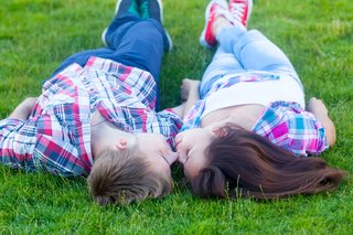 A teen boy and girl lying on grass gently touching their noses together