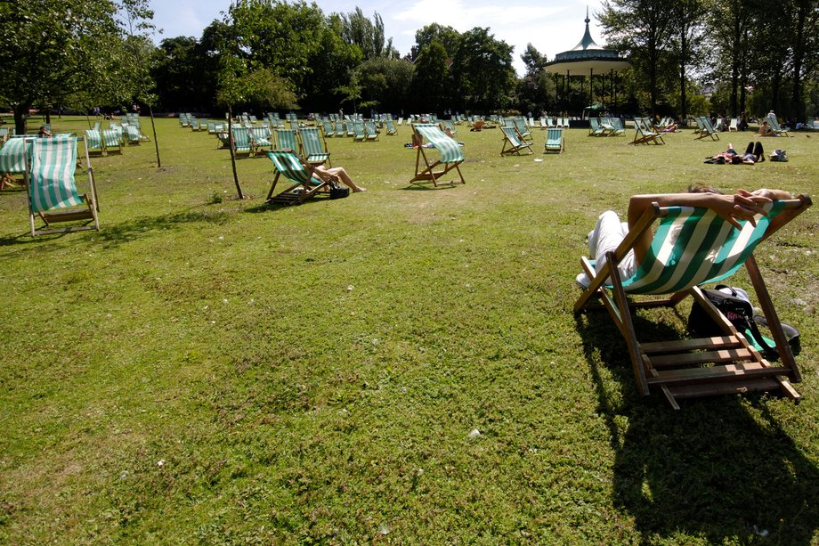 People sitting in deck chairs on the grass in a park on a sunny day