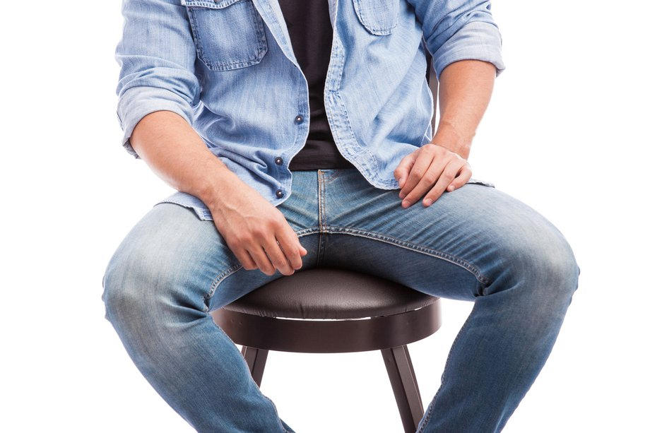 A clothed man sitting on a stool with his legs spread apart